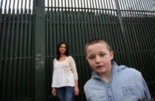 Alison Quinn with her son Cein, 7, who live in the mainly Catholic lower Falls area of Belfast, Northern Ireland, are seen Wednesday, April, 10, 2008. They live in a new development where their house backs on to one of Belfast's many peace walls. Lee Young, 8, and Cein Quinn, 7, live barely 200 yards from each other, but they probably will never meet. Lee is Protestant, Cein a Catholic _ and their communities in Belfast's west inner city are separated by a wall called a peace line. It's nearly 40 years old and 40 feet (12 meters) high. (AP Photo/Peter Morrison)
